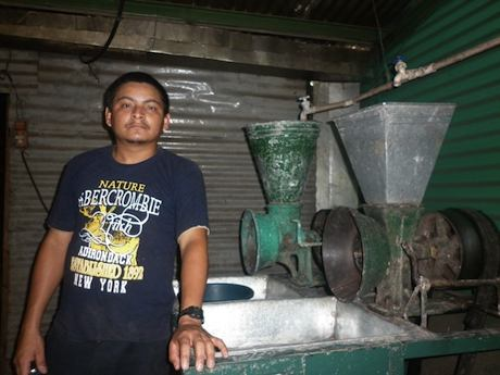 photo of Manuel De Jesus in front of his milling equipment