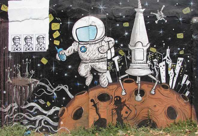 photo of street art of spaceman in space