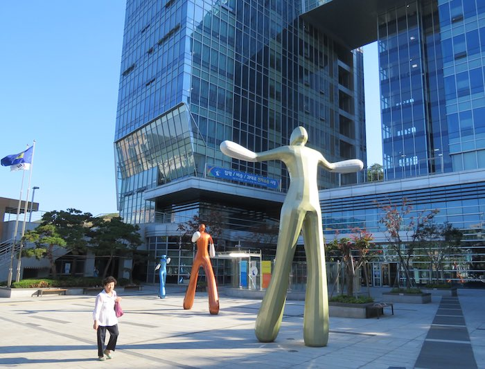 large abstract statues of people in front of a building in Seoul